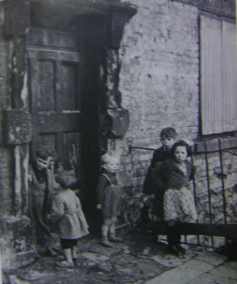 Is there anything to eat, Ma.  Children in front of a tenement in Dublin, Ireland.