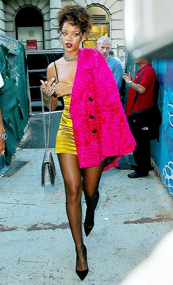 Rihanna showed off her amazing legs in NYC wearing a a gold minidress with a hot pink coat.