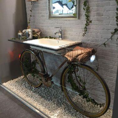Une pièce unique dans la salle de bain avec ce vélo pour support au plan vasque en Corian, le tout posé sur un socle en galet.
