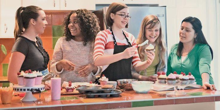 Des adolescentes préparant ensemble des petits gâteaux