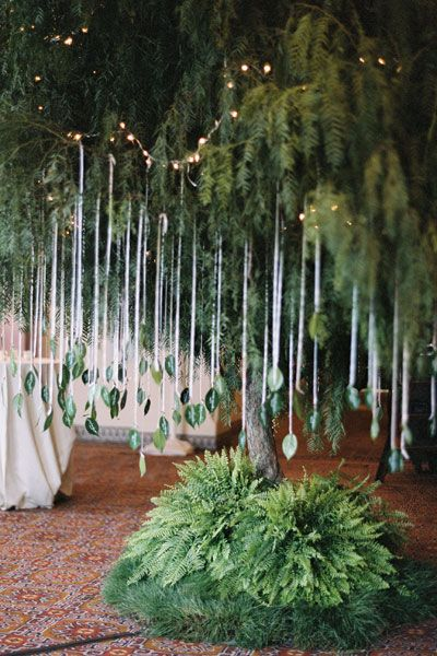 "Put a twist on the ""leaves as escort cards"" idea and, using twine, dangle them from the branches of a lush tree to maximize the foliage effect in an original display. Weave in string lighting to add some twinkle.Related: 35 Cool Ways to Display Your Escort Cards"