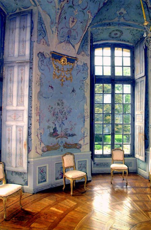 Beautiful old French country house with intricate parquet floors and original hand rolled glass windowpanes. The room is pure Louis XV in style, with walls painted blue and decorated with chinoiserie decor, as are the beautifully painted shutters. The furniture, also Louis XV is simple lines, painted and gilded.