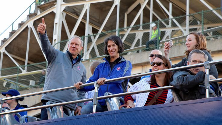 Illinois Gov. Bruce Rauner and his wife Diana greet the crowd outside Wrigley Field as the parade begins. Illinois Senator Mark Kirk watches from the far right. (Evan Garcia / Chicago Tonight)