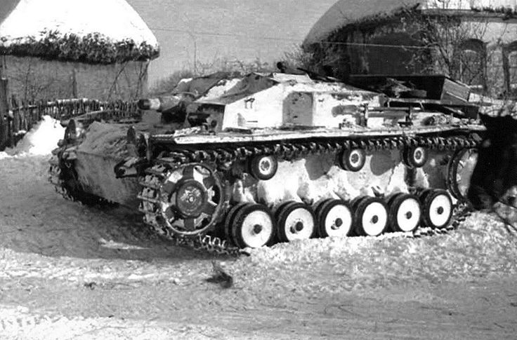 German self-propelled guns StuG III E. StuG III painted in winter camouflage and standing in the street of the Ukrainian village.