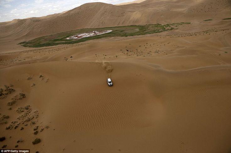 Mini team driver Vladimir Vasilyev and co-pilot Konstantin Zhiltsov past an oasis as they compete in the Gobi Desert in Inner Mongolia