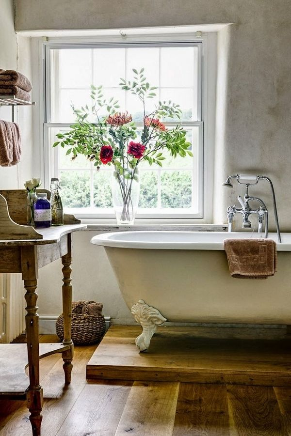 Classic farmhouse bath with wood floors and claw-foot tub (on a pedestal!).