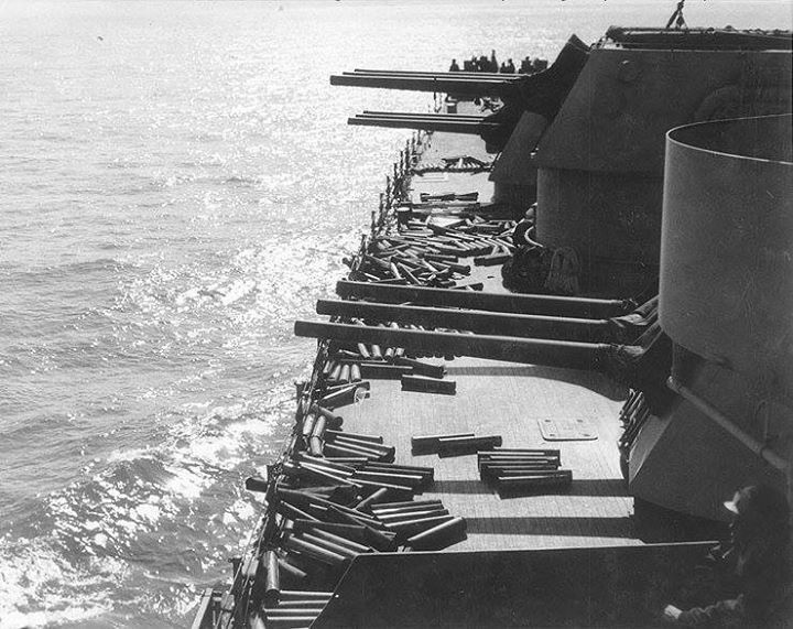 """Empty shell cases litter the deck near the forward 6""""/47 gun turrets of USS Brooklyn (CL-40) after she had bombarded Licata Sicily during the early hours of the invasion 10 July 1943."""