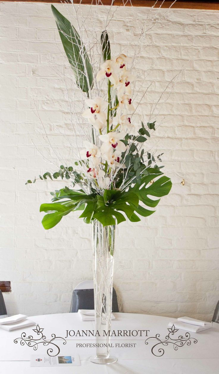 White cymbidium, green and grey foliage, white twigs with silver glitter  arranged in a tall vase.