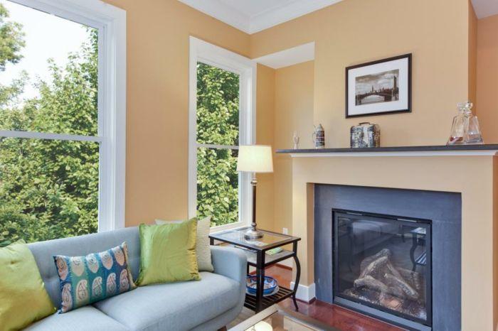 Wandfarbe Apricot, hellblaues Sofa mit bunten Dekokissen - wandfarben fürs wohnzimmer
