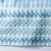 embroidered rows of cross stitch alternated with rick rack on blue gingham.  Very unique