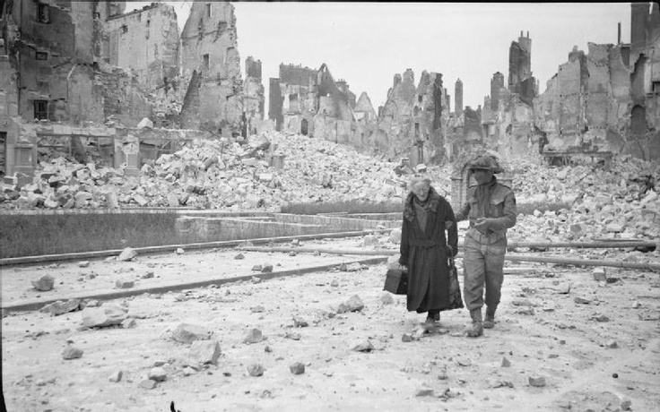 The Battle for Normandy: A British soldier in Caen after its liberation, gives a helping hand to an elderly lady amongst the scene of utter devastation. The town had been substantially destroyed during the bombardment, leaving large numbers of the population homeless. By Capt. E G Malindine, No 5 Army Film & Photographic Unit. (rw)