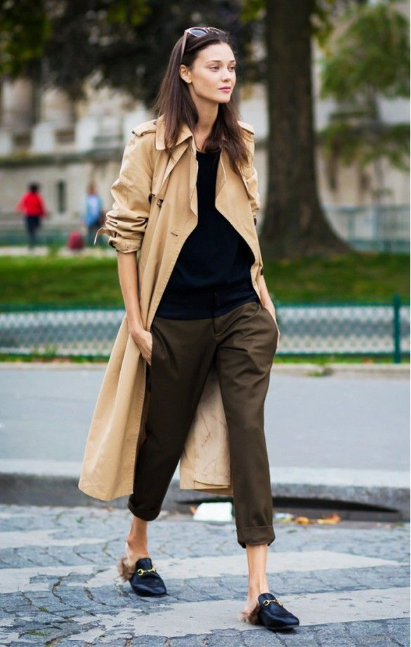 A camel jacket is worn with khaki trousers, a black top and menswear-inspired loafers.