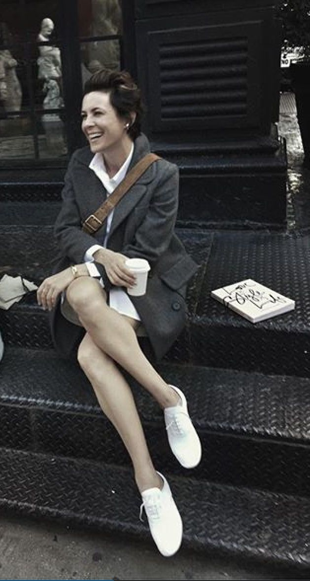 White tennis shoes with rich overcoat and leather accessories