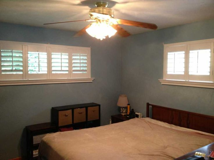 Louverwood plantation shutters on transom windows in a master bedroom.  I love the blue walls!
