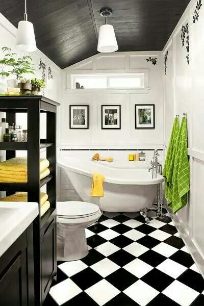 Great use of a small bathroom. Love the black and white tile, the small slipper bath and dash of yellow and green.