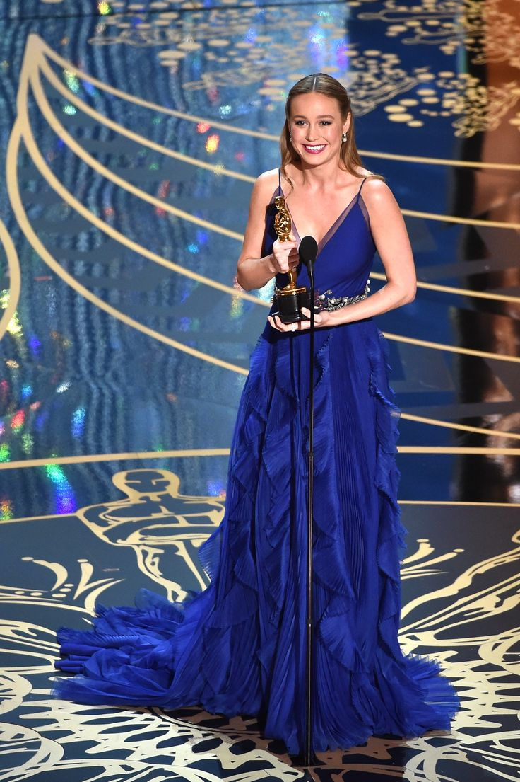 """Brie Larson, awarded for Best Actress for her role in """"Room,"""" attended the 88th Academy Awards in a custom Gucci lapis blue silk organza gown with a plissé and cascading ruffle skirt featuring a navy velvet crystal and pearl embroidered belt with jeweled flowers."""