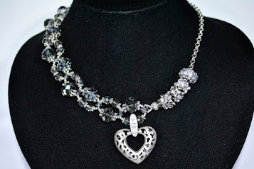 Unique asymmetrical intertwined design made of translucent crystals with a beautiful crystal encrusted heart pendant with chain and crystal encrusted charms.  Approximate width around the neck 48 cm length with pendant 5cm. N126 R350.