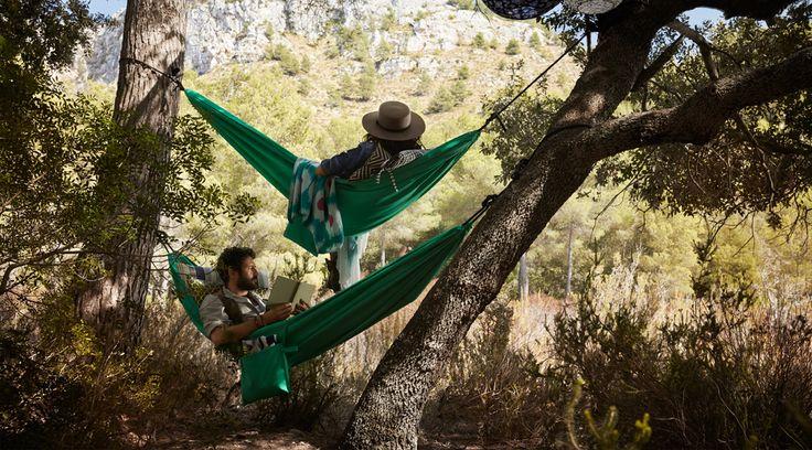 Une femme et un homme se relaxent dans deux hamacs accrochés entre deux arbres.