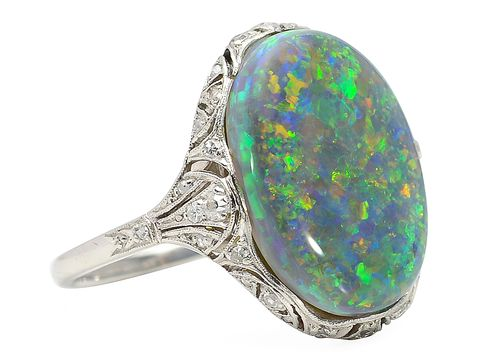 c. 1925 Night Escapade - Black Opal Art Deco Ring. Placed throughout the mount, thirty-two (32) diamonds of a total .29 carats (I-J color; SI1-2 clarity. The black opal flecked with a variety of colors is 6k.