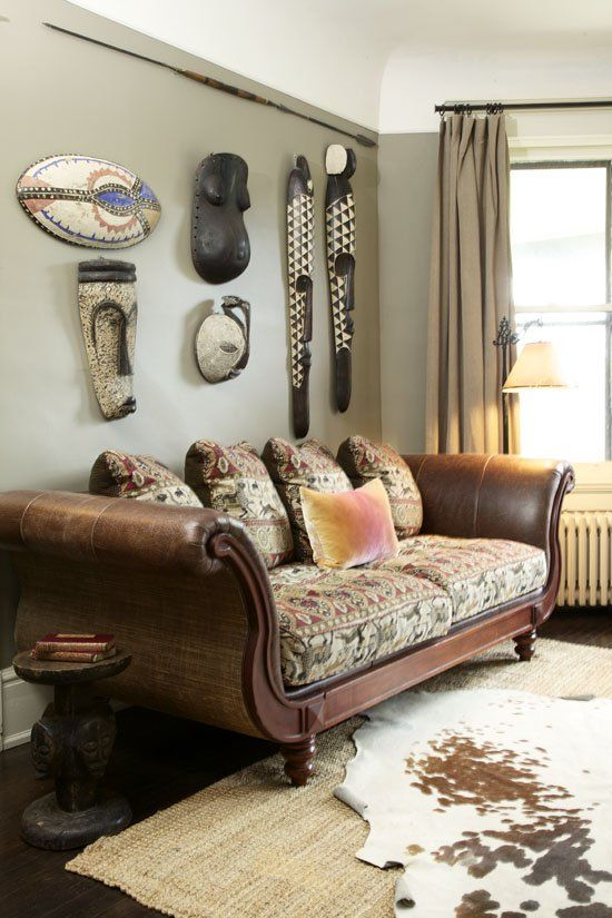 Lovely display of African masks and faux animal skin rug - African living room