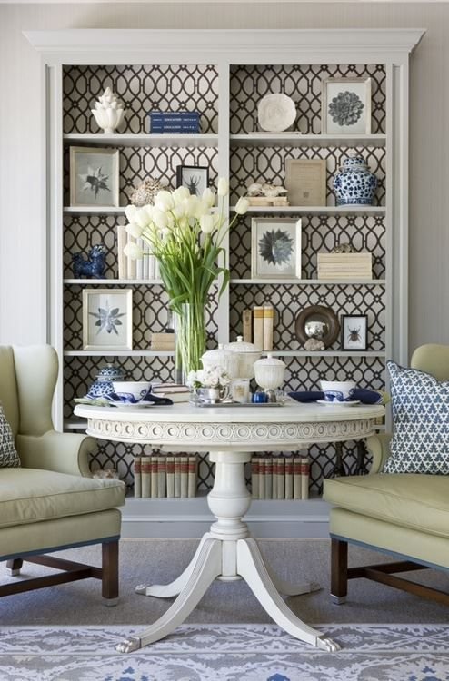 I love the wallpaper back and that the shelves are painted the same color as the wall. Inspiration for my living room bookshelves.     From Manor House Interiors (http://www.manorhouseinteriorsest1992.com).