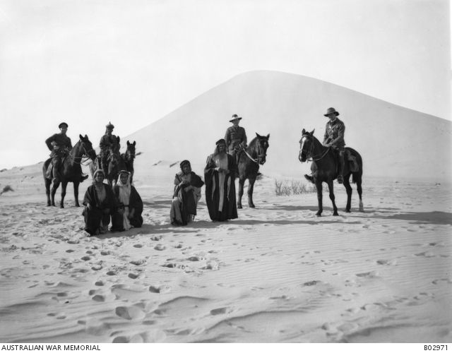 View of Mount Meredith.  In the foreground from left to right mounted are Lieutenant L McCubbin, an Indian Orderly, Lieutenant C Web Gilbert, Lieutenant W W Anderson and four Bedouins.   This photograph was taken to assist the official artist in the construction of the Romani diorama. Egypt: Frontier, Sinai, Romani Area, Romani