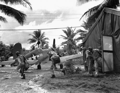 Marine pilots of VMF-214 leave the parachute loft and run to their F4U's at call.