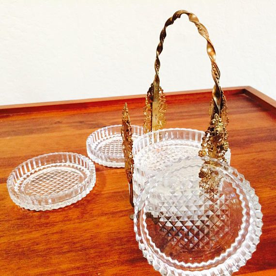 Elegant vintage Hollywood Regency cut glass coaster set with a highly detailed gold ormolu footed caddy. Handle is twisted with intricate detailing. Great looking midcentury bar accessory! Glamorous and useful. Six coasters nestled inside with a cut waffle pattern. Use as a set but