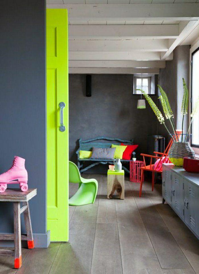 une porte de couleur verte coulissante , murs gris, maison moderne, plante verte