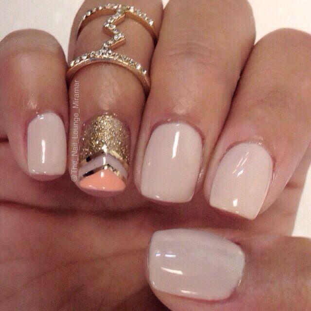 Hermosas uñas en color beige, una de ellas decorada con diseños triangulares con brillos, con líneas doradas y en naranja pastel.