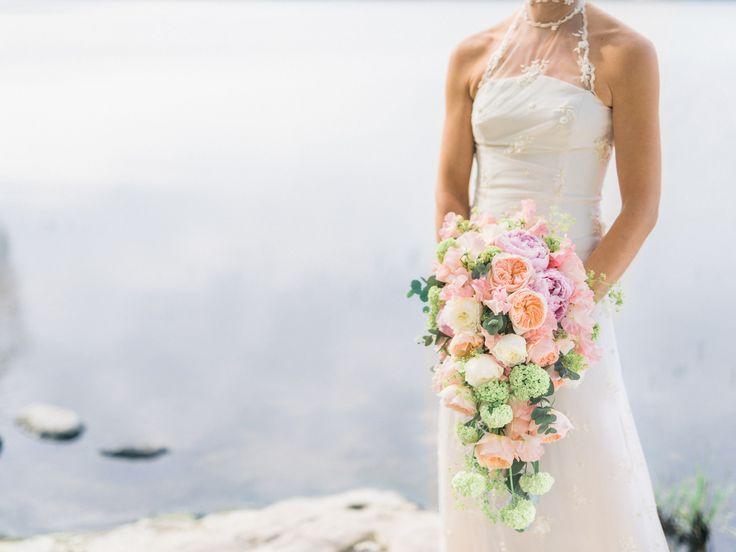 Bruden har en klassisk och vacker droppformad bröllopsbukett med rosor, pioner, trädgårdsrosor, luktärter, eukalyptus och daggkåpa.