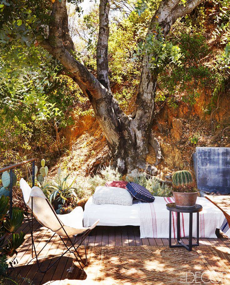 Outdoor lounge area with daybed in forest setting