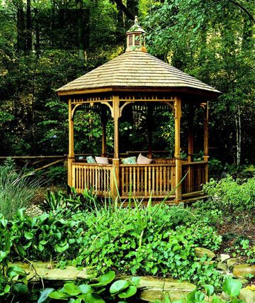 This classic cedar gazebo, constructed with a wood shingle roof, cupola, and Victorian-style bracketing, offers a contemplative resting place in a backyard glade.