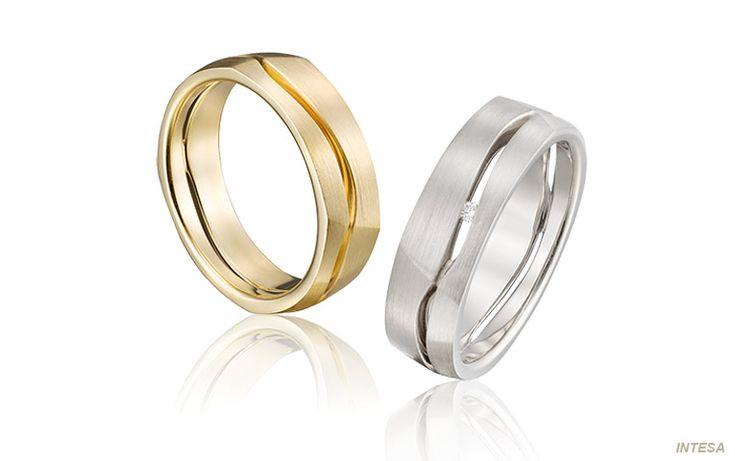 Originele trouwringen in geelgoud en witgoud: twee verschillende kleuren en toch één mooi geheel. De banen van goud verspringen iets en in de damesring is er een diamant tussen gezet.
