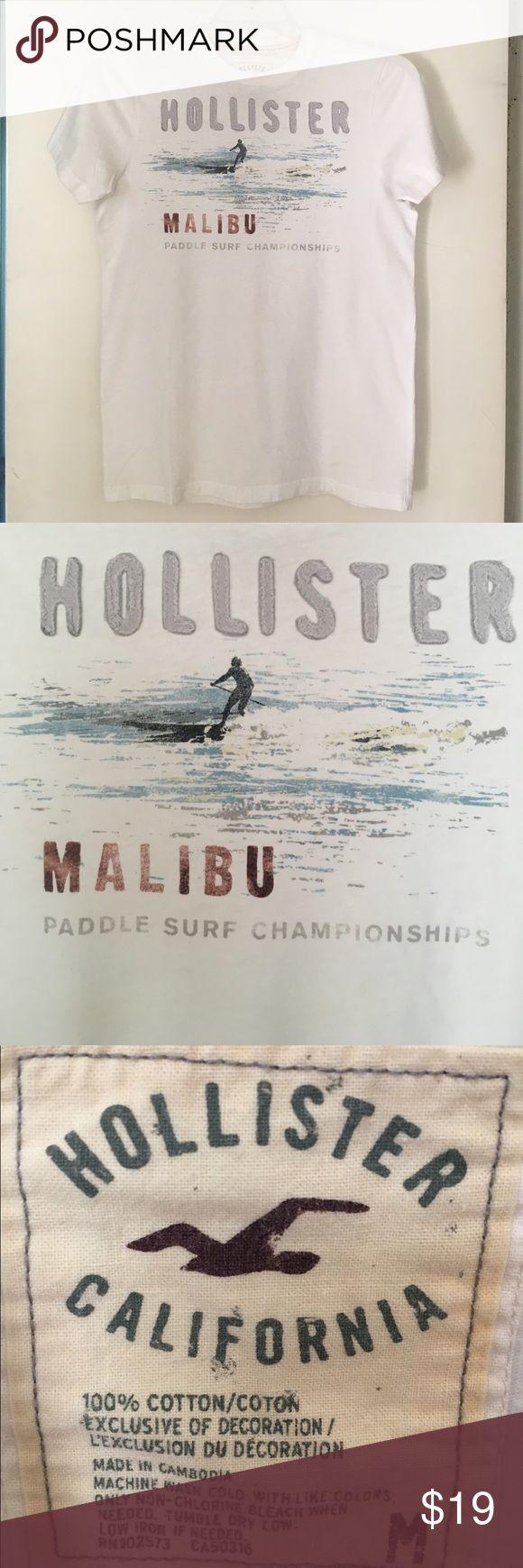 Hollister Malibu Paddle Surf Championship Sz M. Hollister Malibu Paddle Surf Championship Sz M. White w/Dove Gray Raised Lettering & Blue & Gray Paddle Boarding Image. Size Medium. 🚫Trade Hollister Shirts