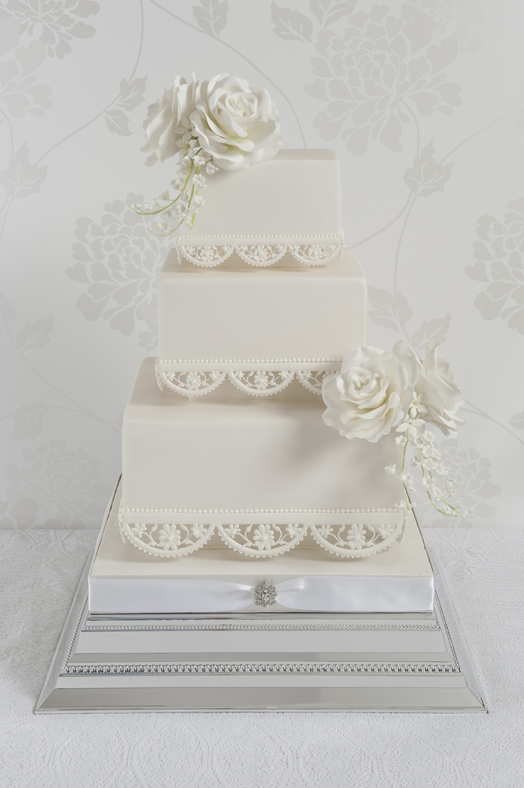 Square 3 tier wedding cake with hand piped lace edging. Adorned with handcrafted sugar roses and Lilly of the Valley.