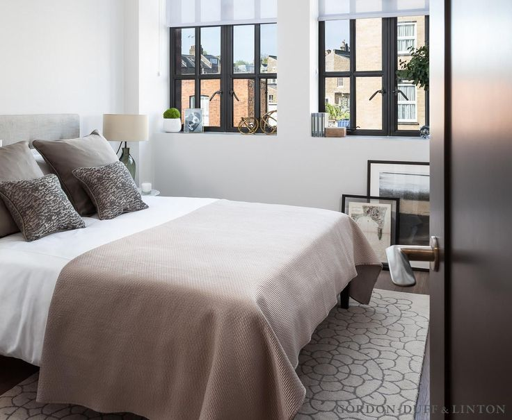 Bedroom in old factory conversion with crittall windows. Velvet headboard. Patterned rug.