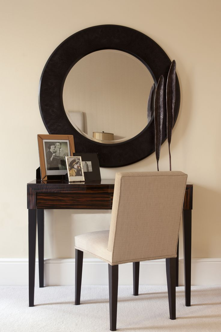 The master bedroom features a dark wall mirror above a coffee-brown dressing table with picture frames and a simple, cream chair. #vanity #bedroom #bedroominterior #wallmirror #carpet #creamwallpaper #frames #pictures