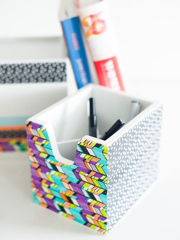 Basic storage boxes are given an update with modern washi tape. Choose one main patterned tape to be the centerpiece, then choose three or four solid, dotted and striped tapes that are similar in color to those found on your main tape. This will create a cohesive look that still appears fresh and trendy.
