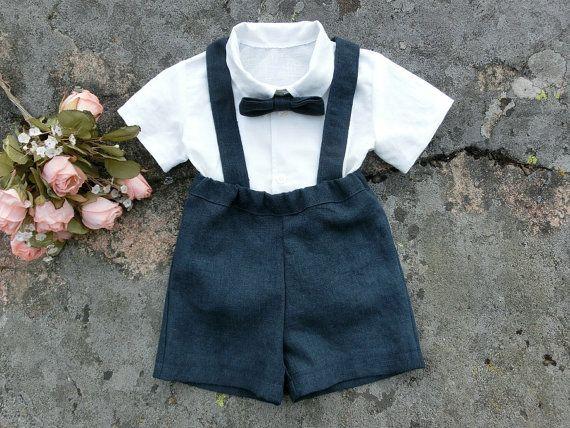 Vestito del ragazzo fatto a mano in lino blu navy con fuori camicia di lino bianco; un look classico per un portatore dellanello rustico o qualsiasi altra occasione formale. Vestito di lino di questo ragazzo è fatto con un sacco di amore e cura.  Questa tuta è costituito da quattro pezzi: una camicia e un paio di pantaloncini con bretelle e un papillon. I pantaloncini sono costituiti da un lino blu navy e la camicia è realizzata in un morbido lino bianco. Bretelle regolabili e rimovibili e…