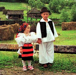 Children dressed in traditional clothes in a typical Maramures landscape