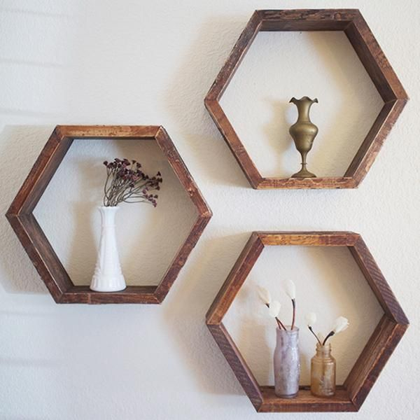 Set of 3 Geometric Wooden ShelvesThese shelves were handmade with wood reclaimed from a vintage piano. Remnants of glue, lacquer finish, and antique stain remain on the wood imparting a charming, rustic look.These shelves work well alone or in a honeycomb grouping.• Each of the 6 sides of the hexagon measures 7 inches long• Shelves are 3-1/2 inches deep• Overall size of each shelf is 14 inches wide by 12 inches tall