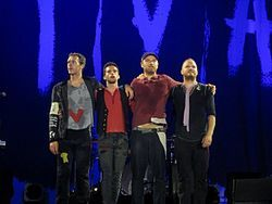 """Coldplay are a British rock band formed in 1996 by lead vocalist Chris Martin and lead guitarist Jonny Buckland at University College London (UCL). After they formed under the name Pectoralz, Guy Berryman joined the group as a bassist and they changed their name to Starfish. Will Champion joined as a drummer, backing vocalist, and multi-instrumentalist, completing the line-up. Manager Phil Harvey is often considered an unofficial fifth member. The band renamed themselves """"Coldplay"""" in…"""