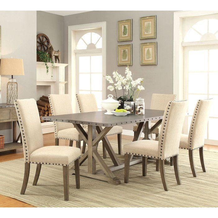 Brighten up your dining room with this transitional style table and chair set. The table features a crafty and simple trestle base with a coastal driftwood finish combined with a metal table top and modern nailhead trim. It is the perfect ingredient to liven up your dining room. The six chairs will add comfort and style to dinnertime. They are padded and upholstered with soft tan fabric and decorated with nailhead trim to complement the table.