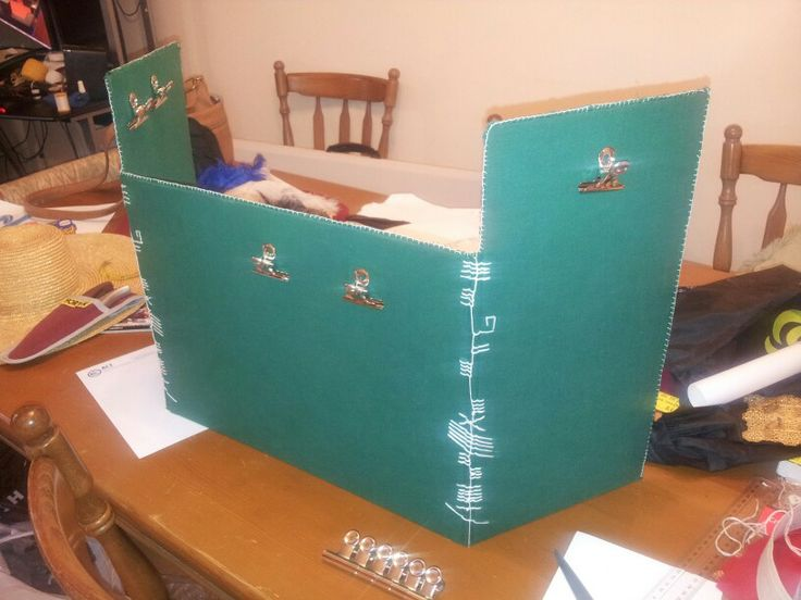 "Game master screen for role-playing. Cotton homespun over painters boards, with magnets to hold document clips. The embroidery reads ""Game Mistress"" in Irish Gaelic, in ogham script. Made for Christmas 2013."