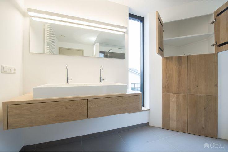 Deze badkamer heeft een rustieke uitstraling door de eikenhouten kenmerken, die overal in de badkamer terugkomen. Doordat er gekozen is voor eikenhouten maatwerk, passen alle elementen perfect in deze mooie ruimte. Zo is er onder de dubbele wastafel een eikenhouten wastafelmeubel geplaatst voor de n…