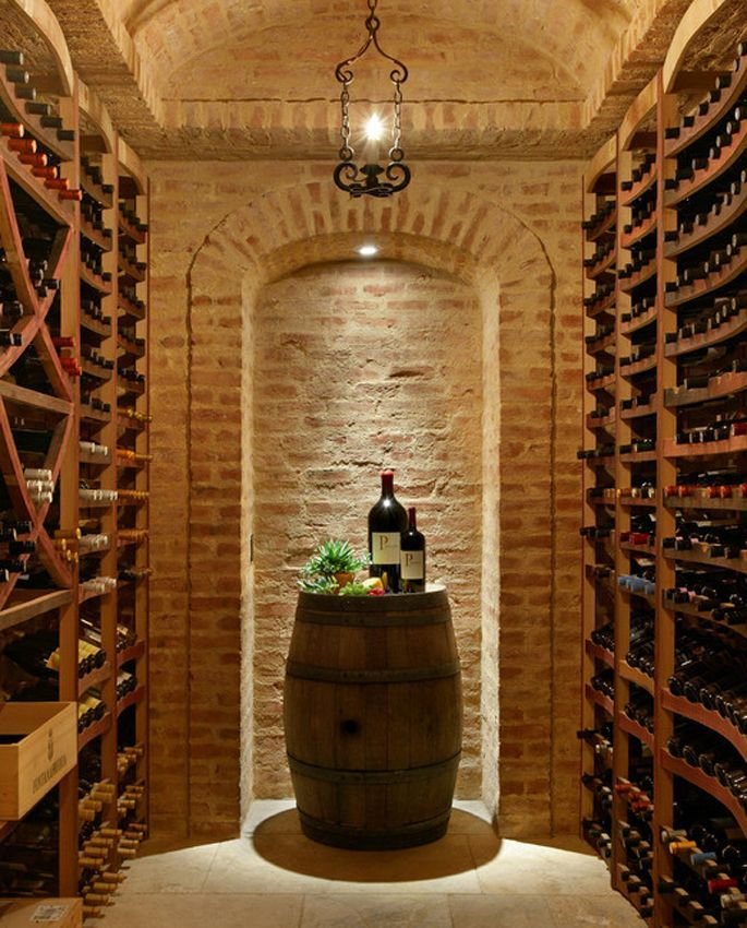 A small, but beautiful wine cellar in light brick. Wooden racks line both sides of the narrow room. A wine barrel serves as a tasting table. Designed by http://www.csceilings.ca/