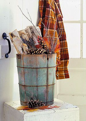 A well-worn wooden bucket serves as a handy storage unit for bundled newspapers and fire kindling.