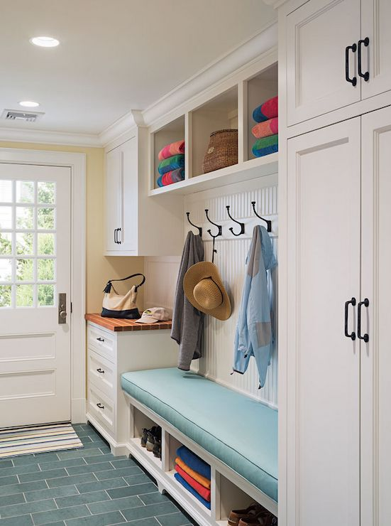 Cottage mudroom features full height shaker cabinets adorned with oil-rubbed bronze hardware beside a built-in bench topped with turquoise cushion under a beadboard backsplash lined with row of hooks under cubbies filled with beach towels next to catchall countertop atop turquoise floor tiles laid out in brick formation.