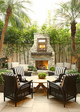 Sitting area with black and white striped cushions, outdoor fireplace - Tim Clarke Design